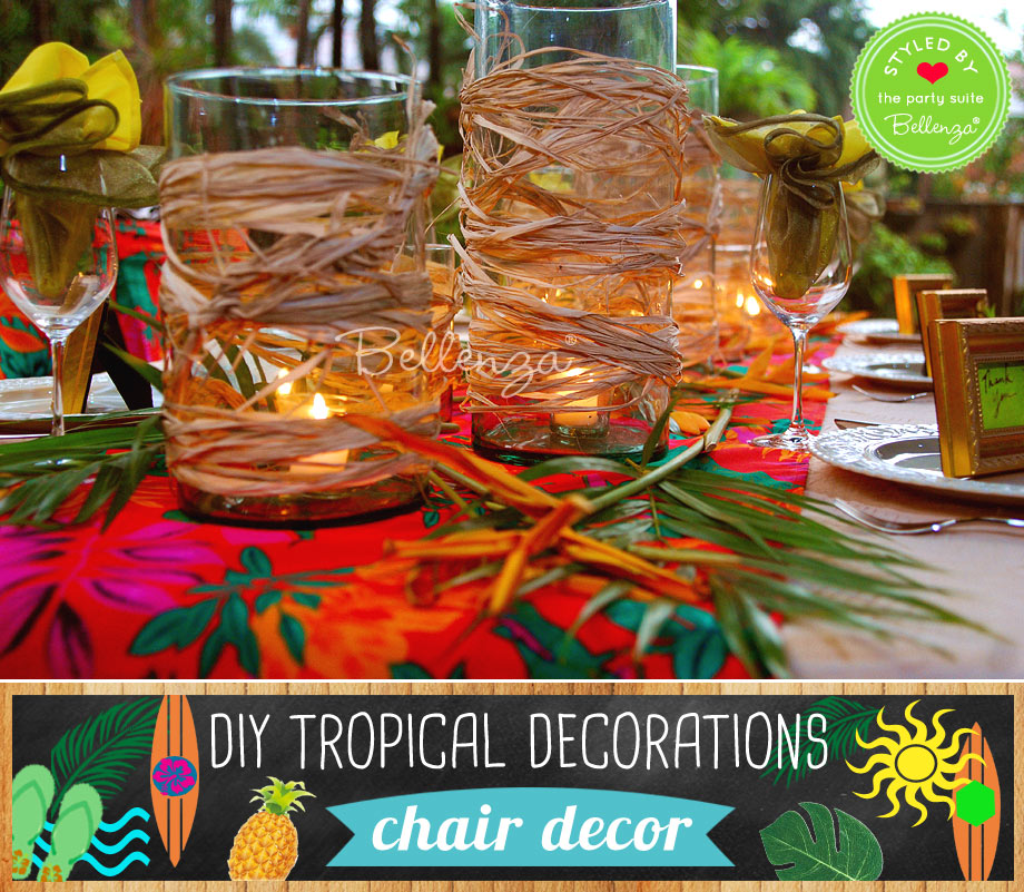 Hurricane glass vases with raffia and tropical leaves.