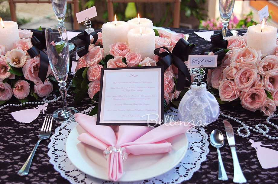 An elegant sweet 16 tablescape with black lace, pearls, and other antique-inspired decorations.