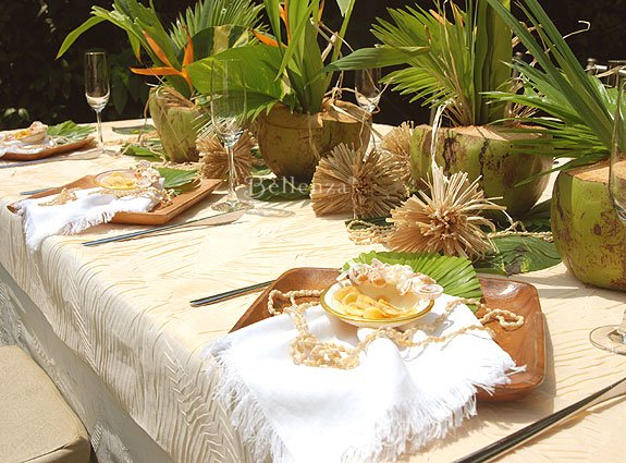Ivory, brown, and tan seaside table setting with tropical accents of wood and leaves.