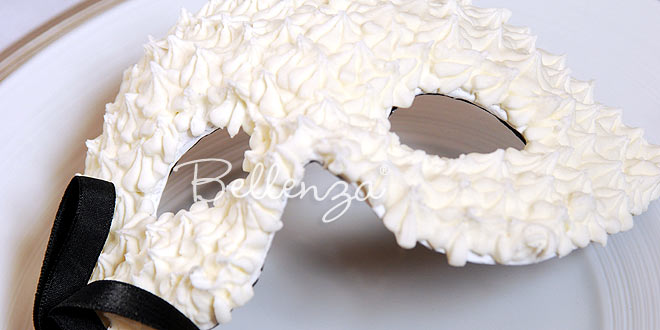 A white mask is laid out as a masquerade ball favor for guests.