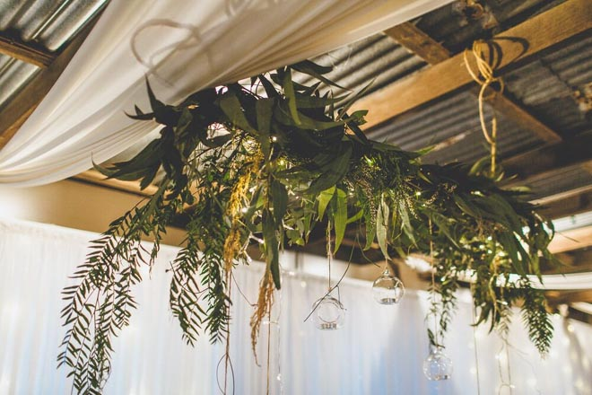 Image provided by Bwedding Invitations. Nathan and Cassie's farm nuptials. Reception decor with lots of greenery.