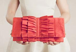 Clutch bag in orange. Photo credit: Ila Handbags