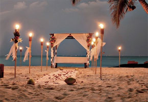 Beach ceremony with tiki lights on aisle