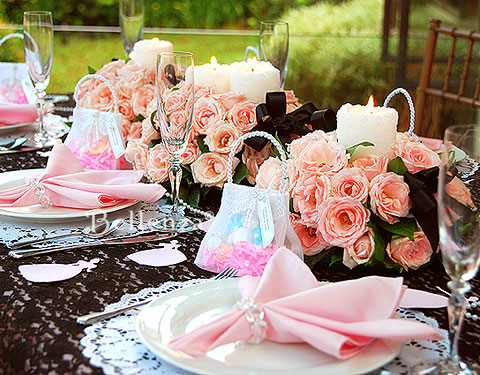 Pink roses, tulle purses, and black lace for a vintage wedding reception