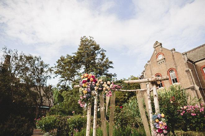 Bright floral ceremony altar in outdoor garden area.