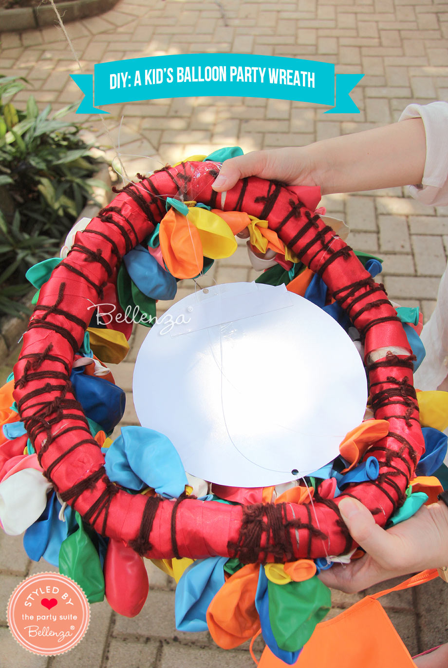 Begin tying the uninflated balloons one by one to the wreath form, using the string.