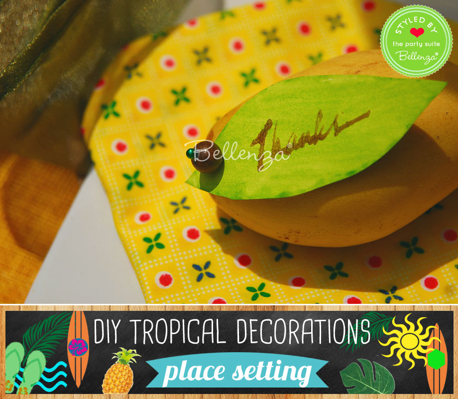 Tropical place setting with yellow napkin and mango with favor tag.