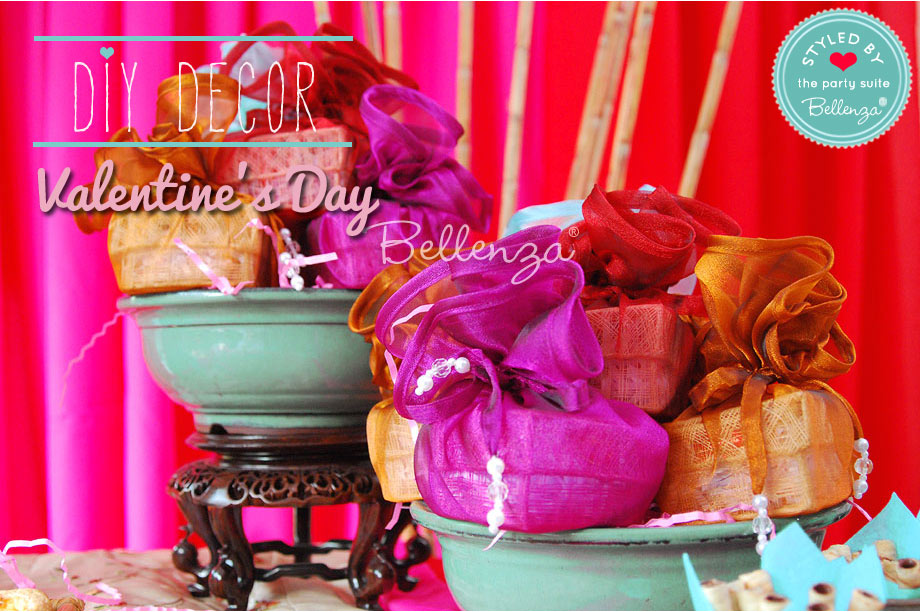 Colorful boxes of cookies in wrapped heart boxes for Valentine's day favors.