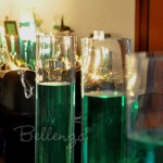 Green colored water centerpieces in tall glass cylinders.