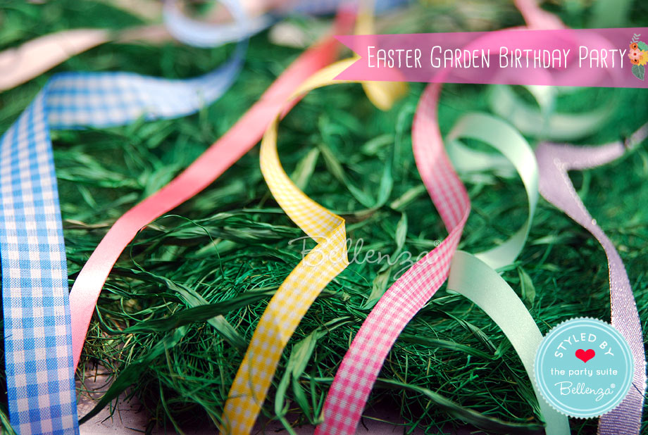 Decorate this table with swirly ribbons, faux grass, and pastel pots to serve as the base for an Easter banner.