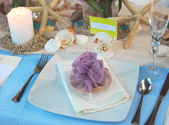 Blue and lilac table setting color palette. Decorated with shells, starfish, candles on sand, and modern accents.