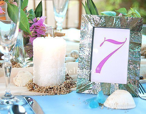 Candles, shells, sand, and green inlaid table number for a seaside tablesetting.