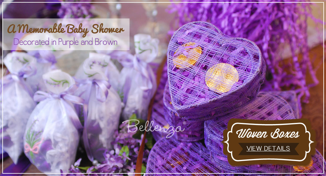 Purple heart favor boxes filled with golden chocolate coins for a baby shower.