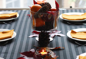 Glass bowl with oranges and pine cones
