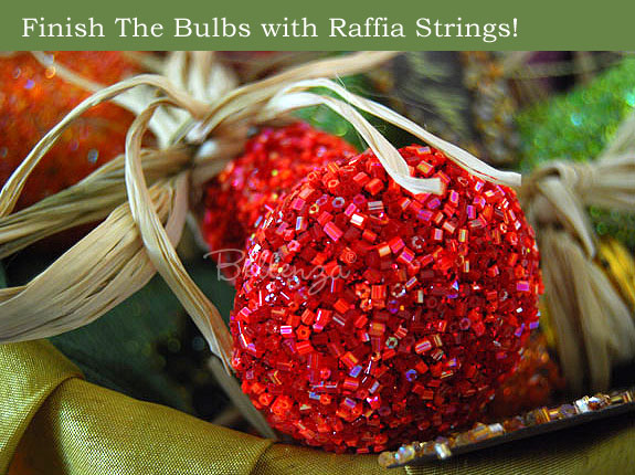 Crafting light bulb with red glitter and raffia