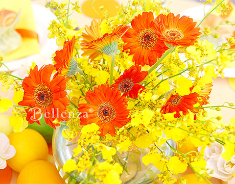 Bright yellow and orange flowers in glass bowl
