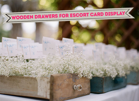 Escort cards displayed in wooden drawers for a rustic garden wedding