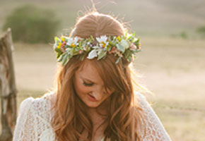 Boho hairstyle with floral crown via Brides.com