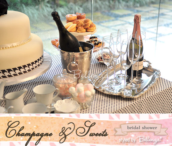 A sweets and champagne dessert table with meringue bonbons, pink-glazed mini donuts, and pink jelly beans.