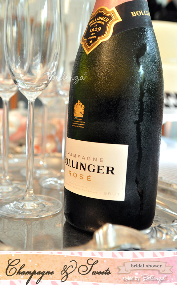A bottle of Bollinger Rosé with a silver tray of champagne flutes
