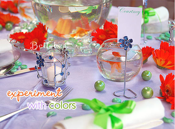 Bright orange florals juxtaposed against blue votives, lime green accents, and a lilac tablecloth.