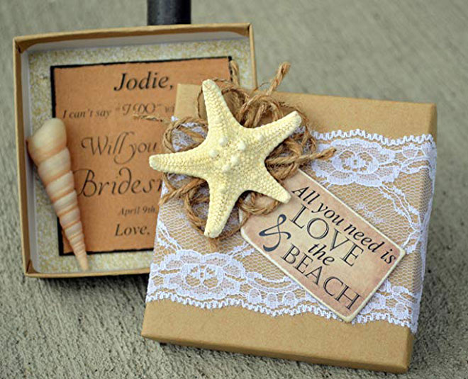 "decorated with a band of lace, a mini knobby starfish, jute cord, and a wooden tag that reads ""All you need is LOVE & the BEACH."""