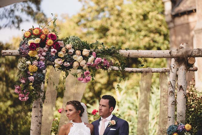 Bright floral ceremony altar in outdoor garden.
