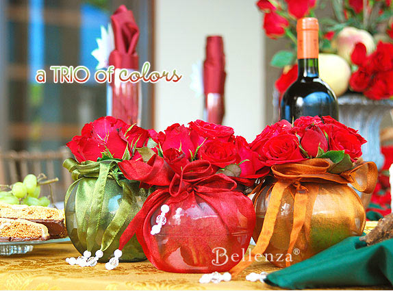 Rich red roses in vessels wrapped in olive green, red, and burnt orange.