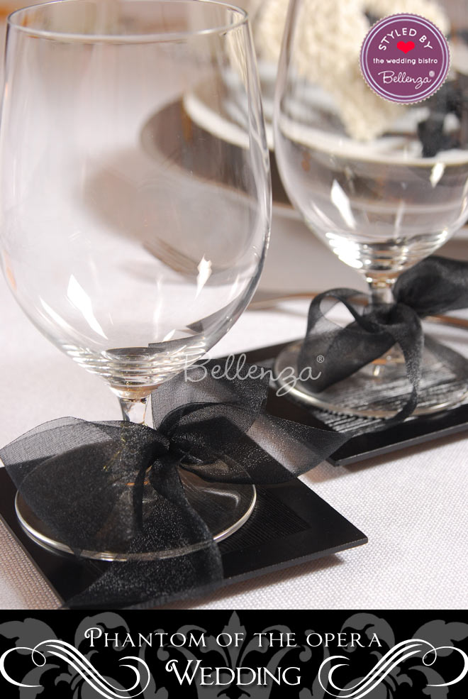 Glasses with black ribbons on a Masqueradeball themed table.