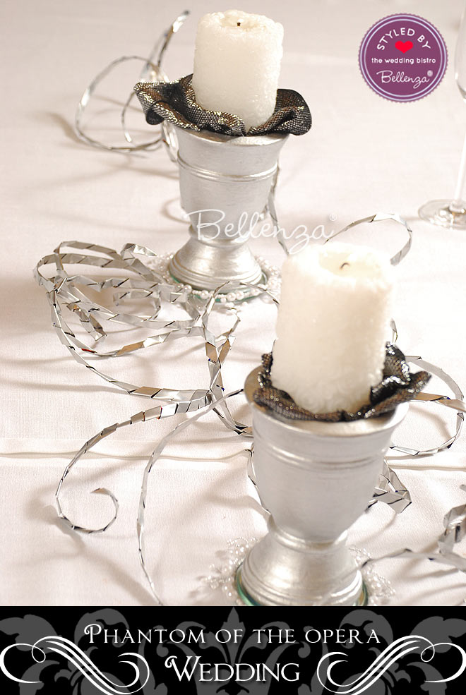 Silver urns serve to hold white candles laid against metallic silver accents.
