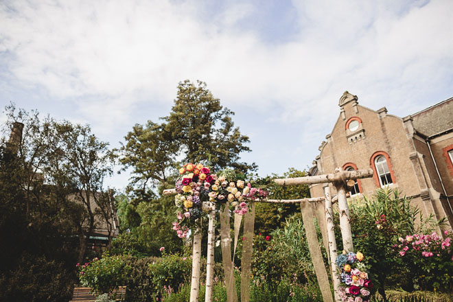 Bright floral ceremony altar in outdoor garden area.
